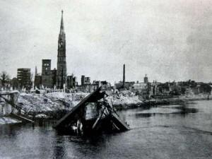 Dieses Bild zeigt die zerstörte Adolf Hitler-Brücke im April 1945. Dahinter die Stephani-Kirche